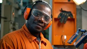 African marine engineer officer in engine control room ECR. He works in workshop with equipment stock video