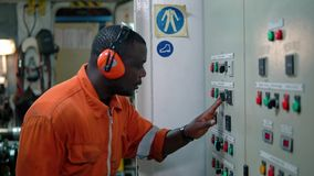 African marine engineer officer in engine control room ECR. Marine engineer officer in engine control room ECR. Seamen`s work. He starts or stops main engine of stock video footage