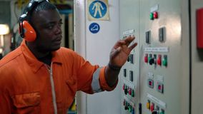 African marine engineer officer in engine control room ECR. Marine engineer officer in engine control room ECR. Seamen`s work. He starts or stops main engine of stock footage