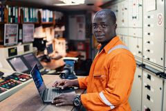 Marine engineer officer working in engine room. African marine engineer officer in engine control room ECR. Seamen`s work. He works at the computer royalty free stock photos