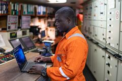 Marine engineer officer working in engine room. African marine engineer officer in engine control room ECR. Seamen`s work. He works at the computer royalty free stock photography