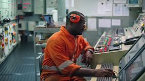 African marine engineer officer in engine control room ECR.