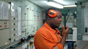 African marine engineer officer in engine control room ECR. He speaks with VHF or UHF portable radio. Ship communication stock video footage