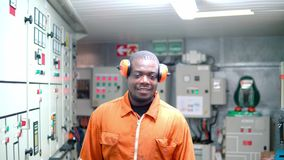 African marine engineer officer in engine control room ECR. He speaks with VHF or UHF portable radio. Ship communication stock video