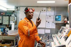 Marine engineer officer working in engine room. African marine engineer officer in engine control room ECR. He speaks with VHF or UHF portable radio. Ship royalty free stock photography