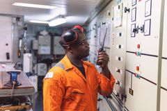 Marine engineer officer working in engine room. African marine engineer officer in engine control room ECR. He speaks with VHF or UHF portable radio. Ship stock photo