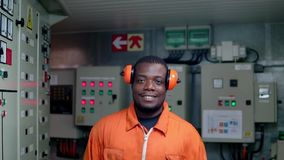African marine engineer officer in engine control room ECR. He walks and looks at the camera stock footage