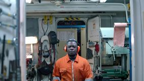 African marine engineer officer in engine control room ECR. He walks and looks at the camera stock video