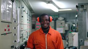 African marine engineer officer in engine control room ECR. He walks and looks at the camera stock video footage