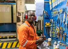 Marine engineer officer working in engine room. African marine engineer officer in engine control room ECR. He works in workshop with equipment stock photography