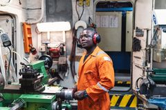 Marine engineer officer working in engine room. African marine engineer officer in engine control room ECR. He works in workshop with equipment royalty free stock images
