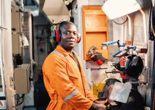 Marine engineer officer working in engine room. African marine engineer officer in engine control room ECR. He works in workshop with equipment stock photos