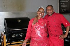 African Market Workers. Two black african cooks, man and woman, with hairnet and in uniforms next to a barbecue in a South African street market called Stock Photography