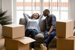 African married couple relaxing after move at new home. Black married couple sitting on couch in living room at house. Smiling happy wife and husband relaxing royalty free stock images