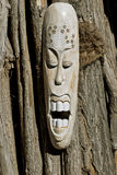 African Mask. African wooden mask on background of big old tree Stock Image