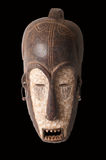 African mask. An African ceremonial mask in the form of a female figure carved in wood isolated on black stock photos