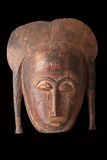 African mask. An African ceremonial mask in the form of a female figure carved in wood isolated on black royalty free stock photography