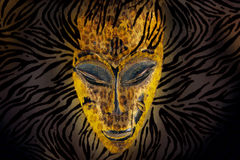 African mask. Old traditional African mask for ceremonies; made of wood, the intense carved face is painted in bright yellow. Combined with zebra and leopard Royalty Free Stock Images
