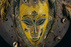 African mask. Old traditional African mask for ceremonies; made of wood, the intense carved face is painted in bright yellow and mounted on a dark wooden support Stock Photos