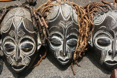 African Masks. Three African masks waiting to be sold by a vendor on the street Royalty Free Stock Photography
