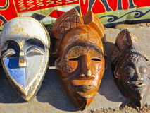African Masks. Closeup of three wooden masks in an outside market in Cape Town, South Africa royalty free stock photography