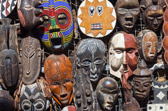 African masks for sell. Traditional african masks hanging for sell in a market stall stock photography