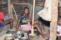 African meal. Anekro, ivory coast-August 20, 2015: girl pounding (foutou) food preferred by many people in Ivory Coast Royalty Free Stock Image