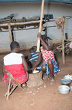 African meal. Anekro, ivory coast-August 20, 2015: an old woman pounding (foutou) food preferred by many people in Ivory Coast Royalty Free Stock Photos