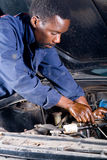 African mechanic. Working on a vehicle royalty free stock photos