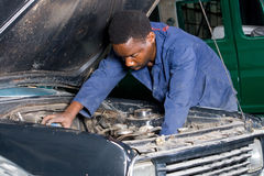 African mechanic repairing a car. African mechanic is repairing a car royalty free stock photo