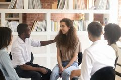 African man psychologist friend supporting caucasian woman sit in circle royalty free stock photos