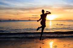 African  men jumping  at Sunset in Tarrafal beach in Santiago is. Land in Cape Verde  Cabo Verde Stock Image