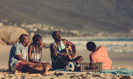 Group of friends having picnic at the seashore. African men playing guitar for friends on the beach. Group of friends having picnic at the seashore royalty free stock photo