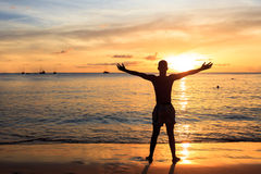 African  men raising arms up  at Sunset in Tarrafal beach in San. Tiago island in Cape Verde - Cabo Verde Stock Image