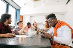 African man is using smartphone while his friends congratulating man Stock Photo
