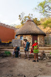 African men and woman standing in front of local hut . Stock Photos