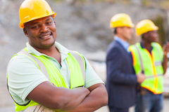 African mine worker. Smiling african mine worker at mining site with colleagues