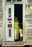 African mother and child. Black mother and child standing in doorway of old wooden house Royalty Free Stock Images