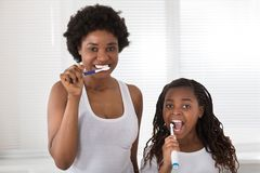 Mother And Daughter Brushing Their Teeth. African Mother And Daughter Brushing Their Teeth In The Bathroom Royalty Free Stock Image