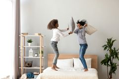African mother and daughter enjoying pillow fight jumping on bed. Babysitter or nanny with teenager girl having fun together at home, older and younger sisters royalty free stock image