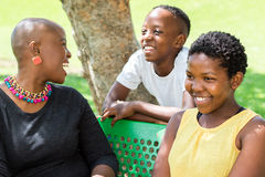 African mother spending time with kids. Close up portrait of young African mother spending quality time with kids in outdoor park stock images