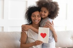 African mum hugging daughter holding greeting card on mothers day stock photography