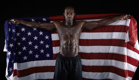 African muscular male holding American Flag stock image