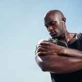 African muscular man listening to music on mobile phone Royalty Free Stock Images