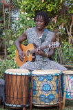 African Musician. Outdoor shot of African musician singing whilst playing the guitar in front of djembe drums Stock Images