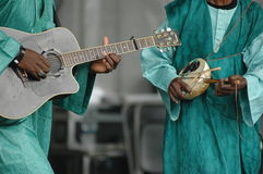 African musicians. Two musicians from a traditional West African band playing a guitar and a njarka fiddle Royalty Free Stock Photos