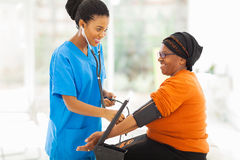 African nurse checking blood pressure. Smiling african nurse checking senior patient's blood pressure royalty free stock images