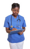 African nurse with clipboard writing message Stock Photo