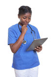 African nurse looking at tablet computer Stock Images