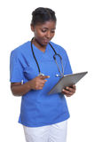 African nurse looking at tablet computer Stock Photos